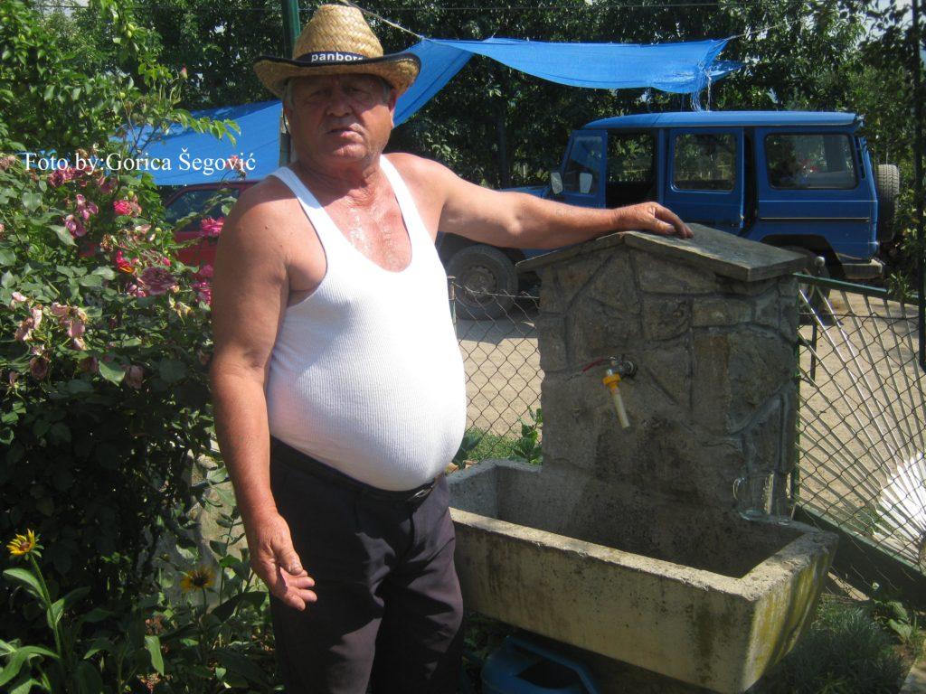 Vucko Savic pored cesme sa koje tece ljuta i meka rakija
